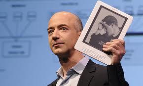 """Jeff Bezos brandit fièrement la tablette numérique d'Amazon : """"le Kindle"""" ."""